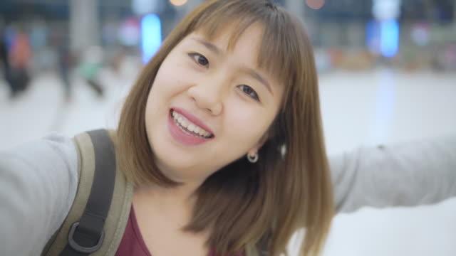 vídeos de stock, filmes e b-roll de slow motion-jovem asiática mochileiros mulher blogger usando câmera fazendo vlog vídeo enquanto espera para o vôo, fêmea em pé no terminal hall no aeroporto internacional. conceito do curso da mulher do estilo de vida. - blogar