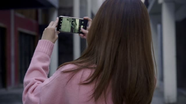 Slow motion - Young Asian blogger woman walking while traveling in the city, beautiful tourist female using smartphone for photo in holidays. Lifestyles woman relax in the city concept.