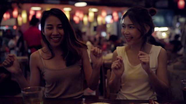 stockvideo's en b-roll-footage met slow motion - jonge aziatische vrouwen backpacker drinken alcohol of bier reizen en dansen met vrienden in stedelijke straat nacht partij bij restaurants in bangkok, thailand. reiziger en toeristische concept. - oost aziatische cultuur