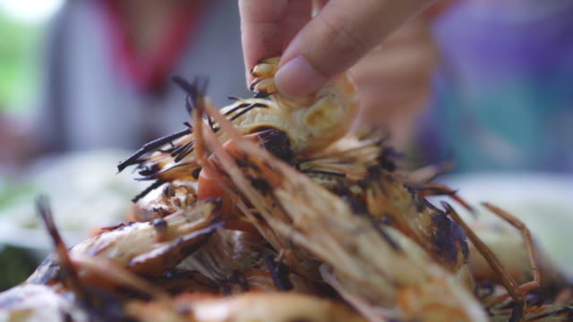 vídeos y material grabado en eventos de stock de slow motion-joven asiática comiendo mariscos camarones en el restaurante, adolescente femenina sintiéndose feliz comiendo comida. mujeres comiendo el concepto de mariscos. - pescado y mariscos