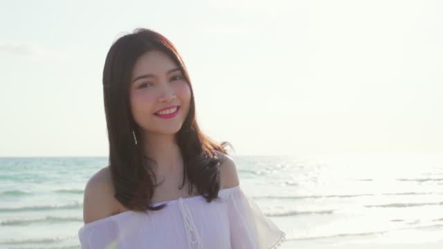 スローモーション-ビーチで歩く若いアジアの女性。夜の日没時に海の近くにビーチで歩いて美しい女性の幸せなリラックス。ライフスタイル女性はビーチコンセプトで旅行します。 - スーパーモデル点の映像素材/bロール