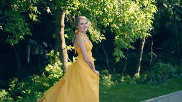 cu, slow motion: ung vacker flicka, i vacker gul fladdrande klänning - aftonklänning bildbanksvideor och videomaterial från bakom kulisserna