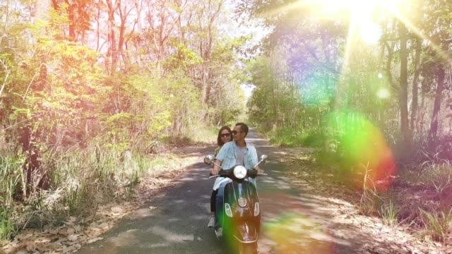 Slow motion Young Couple Riding Motor Scooter Along Country Road video