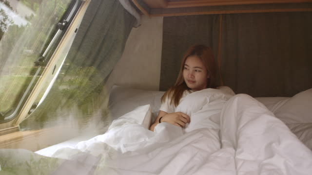 4K Slow motion young female tourist waking up in the morning And stretch There is a little light passing through the window. 4K Slow motion young female tourist waking up in the morning And stretch There is a little light passing through the window. rv interior stock videos & royalty-free footage