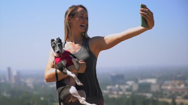 슬로우 모션 젊은 맞는 그녀의 강아지와 그녀의 핸드폰에 아름 다운 selfies를 복용 하는 여자 - influencer 스톡 비디오 및 b-롤 화면