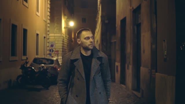 slow-motion. schönen jungen mann zu fuß durch die verlassene straße mit lichtern am abend allein - introspektion stock-videos und b-roll-filmmaterial