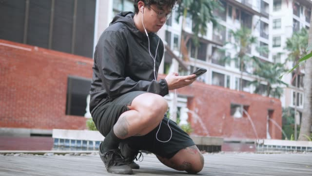 slow motion : young healthy indie asian man stretching listening music, wacthing vdo and chat on smart phone on swiming pool. - pantaloncini video stock e b–roll