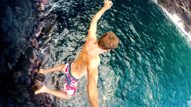POV Slow Motion Young Man Jumping from cliff into the ocean. Extreme Cliff Jump Fun Summer Lifestyle Slow Motion GOPRO POV Young Man Jumping from cliff into the ocean in Hawaii. Summer fun lifestyle. Beautiful Blue Ocean Big Sea Cave in Background. SLOW MOTION cliff jumping stock videos & royalty-free footage