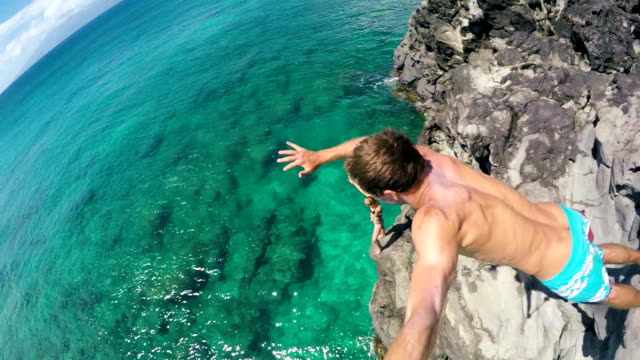 POV Slow Motion Young Man Jumping from cliff into the ocean. Extreme Cliff Jump Fun Summer Lifestyle