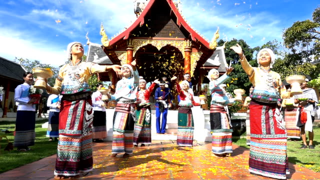 slow motion young men and women wear traditionnel thai dress dancing and strew orchid flower in the temple - cultura tailandese video stock e b–roll