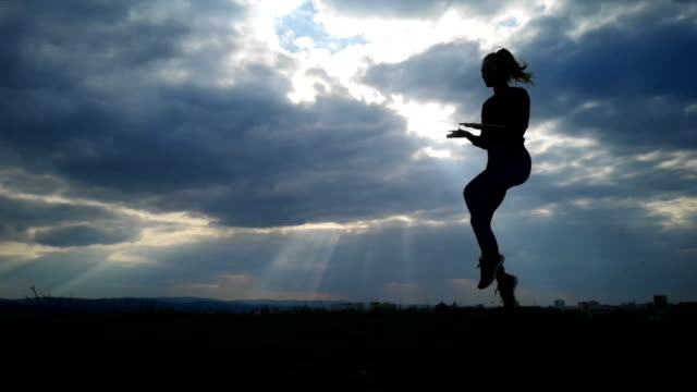 Bидео Slow Motion young woman exercising at park silhouette. Fit young woman doing training workout Slow Motion. Young happy woman stretching at the park after a running workout. Exercise outdoor concept.