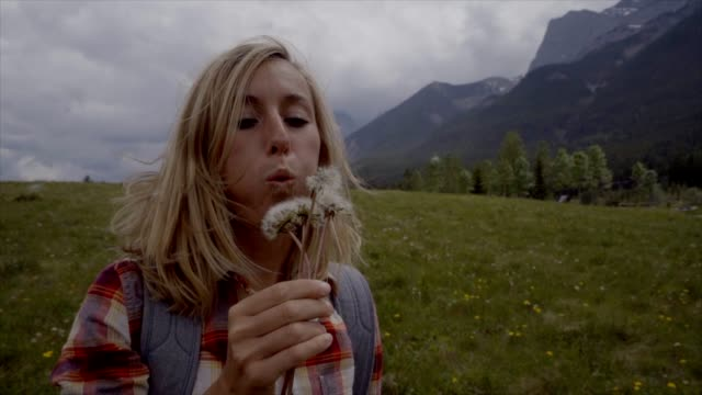 Slow motion- Young woman is blowing Dandelion seeds into the air video