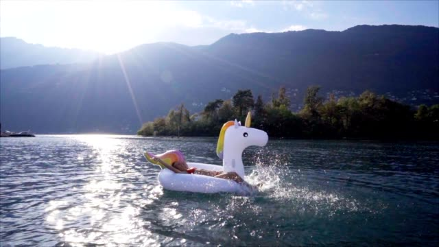 Slow motion: Young woman on an inflatable unicorn having fun in the water Slow motion: Young woman on an inflatable unicorn having fun in the water only young women stock videos & royalty-free footage