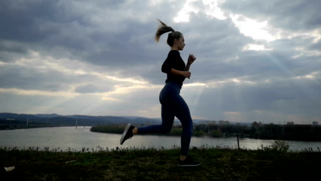 Bидео Slow Motion young woman running at sunset, Young woman running silhouette. Jogging slow motion, beautiful clouds, Athletic Woman Working Out outdoor