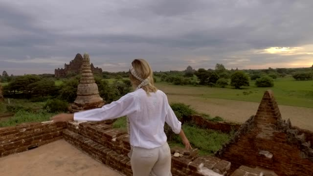 Slow motion, young woman running on top of ancient Buddhist temple in Bagan, Myanmar Slow motion, young woman running on top of ancient Buddhist temple in Bagan, Myanmar bagan stock videos & royalty-free footage