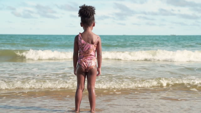 Slow motion,An African-American girl standing and looking at the waves on the beach