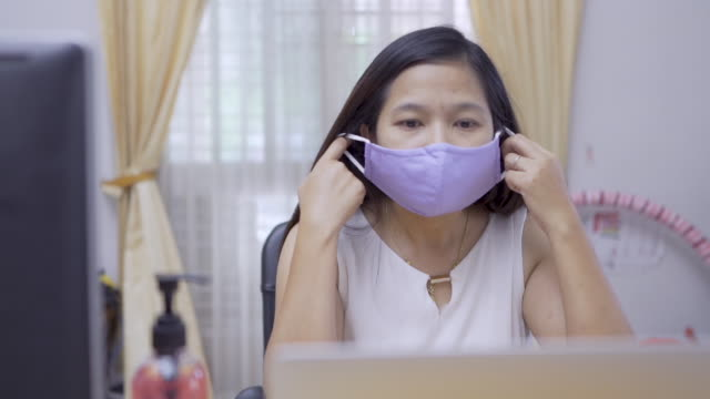 Slow motion,Girl removing mask, feeling comfortable, working at home - vídeo