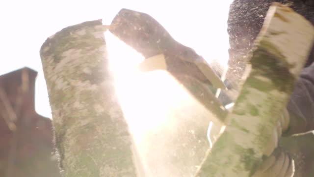 ağır çekim: ahşap bir balta ile güneş arka plan ile bölme - şömine odunu stok videoları ve detay görüntü çekimi