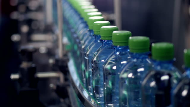 a slow moving conveyor with pet bottles ready for labeling. - plastic stock videos and b-roll footage