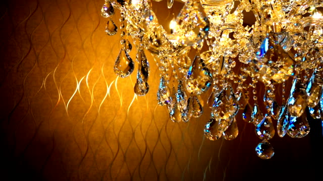 slow moving of Brilliant crystal chandelier hanging on ceiling with  filter color effect  in a luxurious interior video