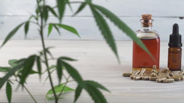 långsam panorera från cannabisblad till cannabis olja flaskor, cbd kristaller och cbd piller på träbord - thc bildbanksvideor och videomaterial från bakom kulisserna