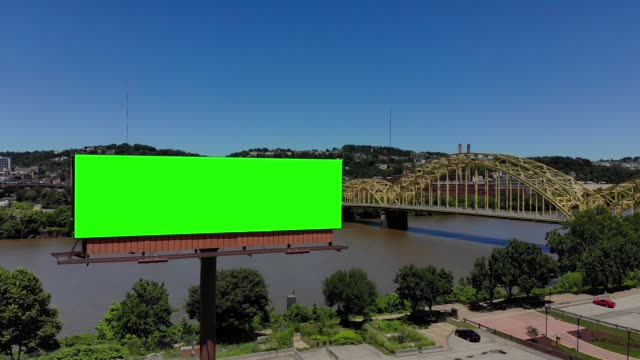 Slow Push Forward Aerial View of City Green Screen Billboard A slow push forward aerial view of a city's billboard. Green screen with optional tracking points for advanced screen replacement. 16th Street Bridge over the Allegheny River in the background. billboard stock videos & royalty-free footage