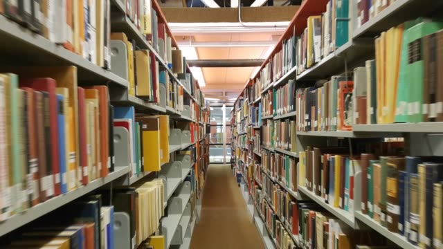 Slow push-in of an aisle in a library slow push in movement in an aisle of books in a library textbook stock videos & royalty-free footage