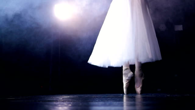 Slow steps on dancing pointe shoes under a spotlight. video