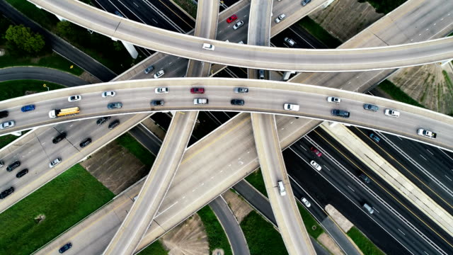 Slow turning as Traffic drives across Futuristic Transportation Highway and Modern infrastructure aerial drone view Top Down , looking straight down , Slow turning as Traffic drives across Futuristic Transportation Highway and Modern infrastructure texas stock videos & royalty-free footage