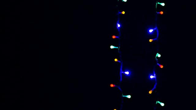 langsam blinkende weihnachtslichter auf dunklem hintergrund - girlande dekoration stock-videos und b-roll-filmmaterial