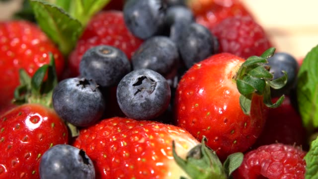 vídeos y material grabado en eventos de stock de lentamente paneo sobre frambuesas frescas, arándanos, fresas. surtido de bayas como fondo alimenticio. 4k - antioxidante