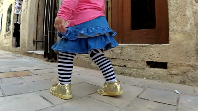 slow-mo baby girl walking along the narrow street of the old town - mika video stock e b–roll
