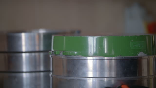 Slow-mo: Beautiful Woman Laboratory Technician Close Silver Strainer Barrel With Belts