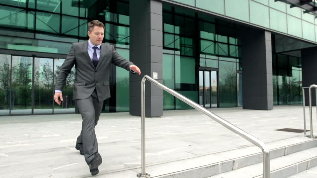 Slow-Mo: Businessman Slides Down The Rail And Falls.