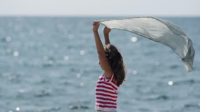 медленно-mo: маленькая девочка держит шелковый шарф на море против ветра - шарф стоковые видео и кадры b-roll