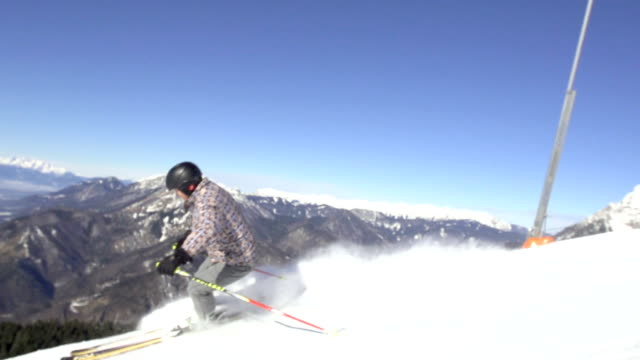 Slow-Mo: Male Skier Stops On Ski Slope With Mountain View video