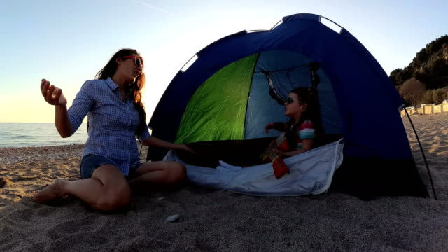 slow-mo mother and daughter playing a guitar on the beach - mika video stock e b–roll