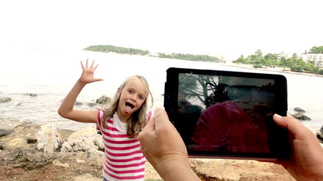 slow-mo: mother taking a picture of her daughter on beach - eksantrik stok videoları ve detay görüntü çekimi