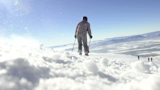 slow-motion: vista posteriore di sciatore sci discesa - sci freestyle video stock e b–roll