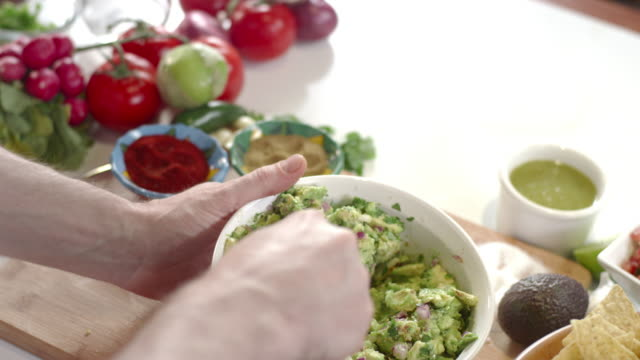 Slow-mo shot of chef mixing large bowl of guacamole Slow-mo shot of chef mixing large bowl of guacamole dipping sauce stock videos & royalty-free footage