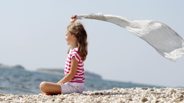 Slow-Mo: Smiling Girl Sitting Silk Scarf Flowing By The Sea video