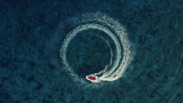 slowmotion luftaufnahme eines schnellen schnellbootes mit einem roten dach, das im kreis herumfährt und schöne donuts im klaren türkis-magischen meer macht. - kreis stock-videos und b-roll-filmmaterial