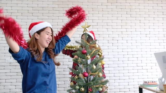 office.xmas ホリデイ ・ celebration.creative 事務所のクリスマス パーティーで踊る見掛け倒しとサンタの帽子とスローモーション アジア女性 - サンタの帽子点の映像素材/bロール