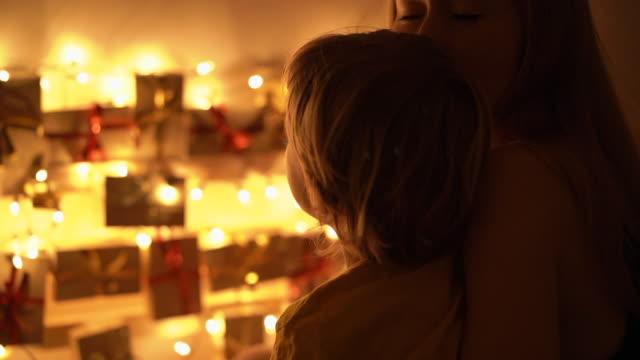 slowmotion nahaufnahme von einer mutter und ihrem kleinen sohn blick auf einen adventskalender hängen deiner bett beleuchtung mit weihnachtsbeleuchtung. vorbereitung auf weihnachten und neujahr konzept. adventskalenderkonzept - adventskalender stock-videos und b-roll-filmmaterial