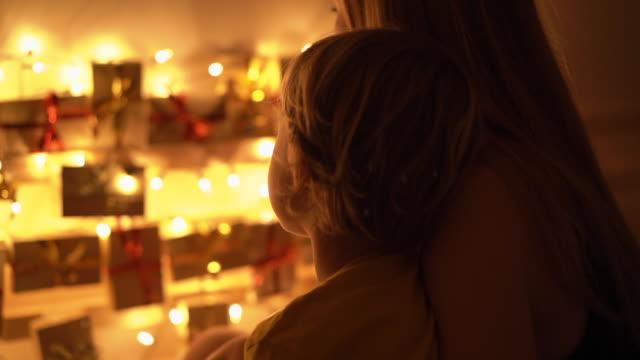 slowmotion nahaufnahme von einer mutter und ihrem kleinen sohn blick auf einen adventskalender hängen deiner bett beleuchtung mit weihnachtsbeleuchtung. vorbereitung auf weihnachten und neujahr konzept. adventskalenderkonzept - advent stock-videos und b-roll-filmmaterial