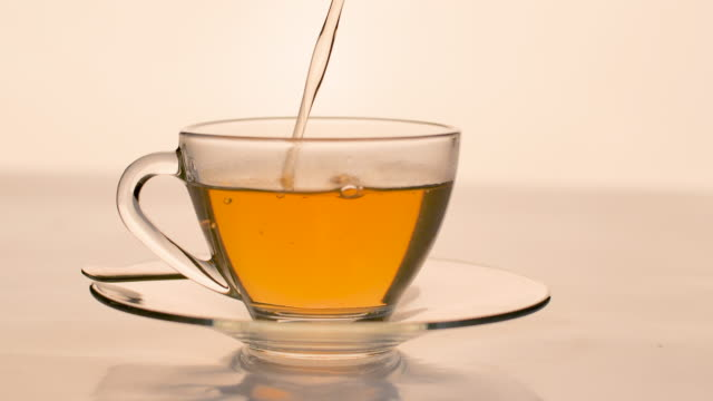 slow-motion. close-up tea pouring into a clear glass on the table. - teapot stock videos & royalty-free footage