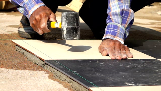 slow-motion, construction worker using hammer tiling floor video