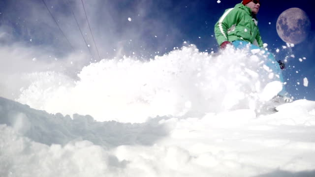 Slow-motion dynamic footage of a skier going down the slope : snow flies into the camera video