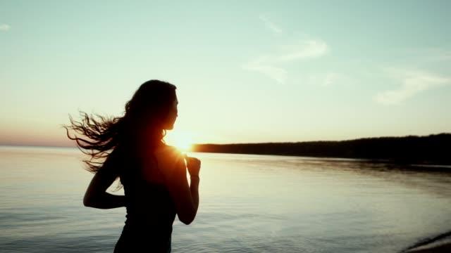 vidéos et rushes de slowmotion. soirée jogging le long du front de mer - joggeuse