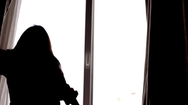 Slowmotion footage of a female silhouette opening up the curtains and looking down the balkony. video